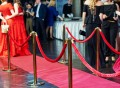 50038038 - event party. red carpet entrance with golden stanchions and ropes. guests in the background